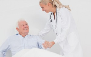 Doctor helping elderly man in bed to sit up